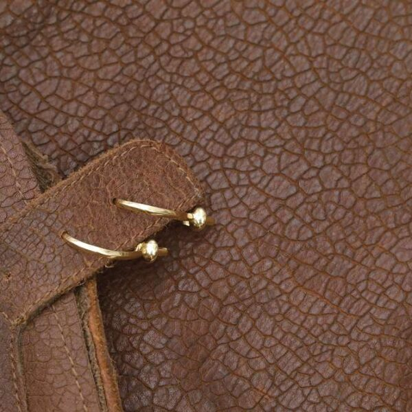 The 5Touches Earrings on brown leather.